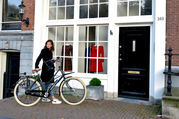 Girl with bicycle at shop in Amsterdam